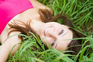 Woman Laying Content in Grass - How to Use Nature to Relieve Stress- Natural stress relievers, natural ways to relieve stress, stress relief activities, fun stress relieving activities, reduce stress naturally, nature help us, outdoors and mental health